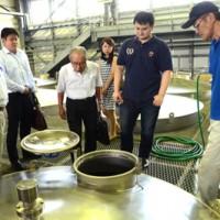 焼酎工場を見学するロブションさん(右から2人目)ら=22日、龍郷町