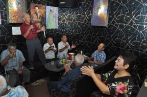最高齢87歳の末川さんの歌で盛り上がるカラオケ仲間=14日、和泊町手々知名