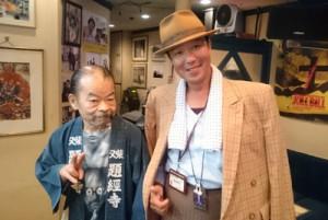 佐藤蛾次郎さん(左)と記念撮影する辻寅さん(本人提供)