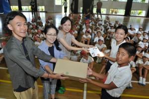 児童代表に絵本を手渡す(左から)山田さん、松村さん、横山さん=8日、知名町の下平川小