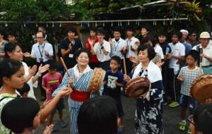 研修で来島した鹿大生も交えてにぎやかに歌い踊った佐仁の八月踊り=7日、奄美市笠利町