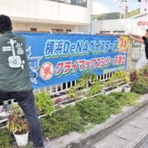 横浜DeNAベイスターズのクライマックスシリーズ出場を祝う横断幕を設置する職員=30日、奄美市役所の仮庁舎