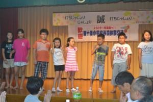歓迎交流会で自己紹介する東十条小の児童ら=8月27日、与論町茶花自治公民館
