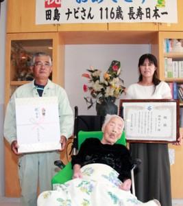 県から祝い状贈呈などを受けた国内最高齢の田島ナビさん(中央)と孫の廣行さん、由起子さん夫婦=15日、喜界町