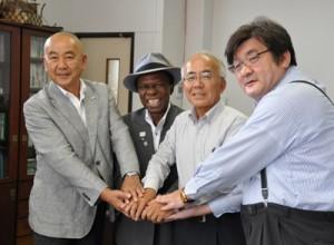 覚書を交わして握手する大久保明町長(中央右)とオスマン・サンコンさん(同左)ら=2日、伊仙町