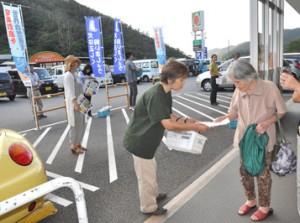 買い物客にチラシを配布するノイヌ・ノネコ対策検討会の会員ら=21日、奄美市名瀬