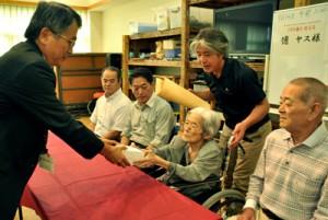 100歳の長寿祝い品を受け取る徳ヤスさん(右から2人目)=14日、龍郷町