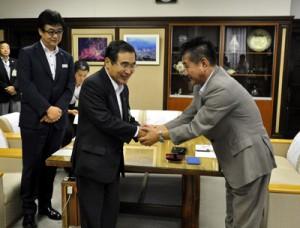 協定書の調印後、固く握手を交わす米澤亮治社長(右)と森博幸鹿児島市長=2日、鹿児島市役所