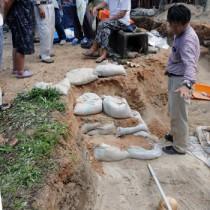 発見された人骨について住民に説明する竹中教授(右)=11日、宇検村屋鈍