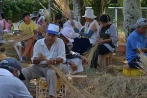 大綱用の稲わらを整える住民=4日、与論町城