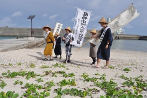 上陸地の伊延の浜を出発する西郷隆盛役と役人役の一行=9日、和泊町伊延
