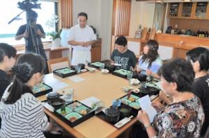 昼食で店主(中央)のメニュー説明に聞き入るモニターら=25日、和泊町和泊