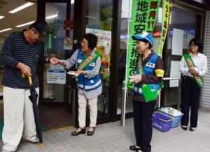 街頭でチラシを配る奄美署員と地域安全安全モニター=14日、奄美市名瀬港町