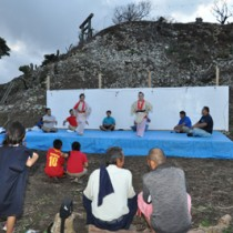 本番会場の広場に組んだ舞台で稽古する劇「世之主」出演メンバーら(上)と演舞練習に取り組む「北山の風」出演の生徒ら=23日、和泊町内城