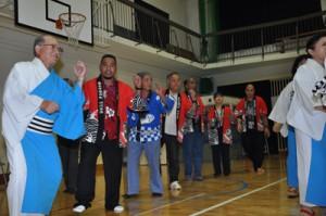 川内集落住民らと八月踊りを楽しむ外国人研修生=30日、東城小中体育館