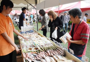 奄美産の商品を手に取る買い物客=12日、鹿児島市の鹿児島中央駅アミュ広場