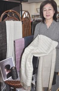 県知事賞を獲得した「amamika(アマミカ)ショール」を手に受賞を喜ぶ興紬商店の興ほずみ専務取締役=11日、龍郷町