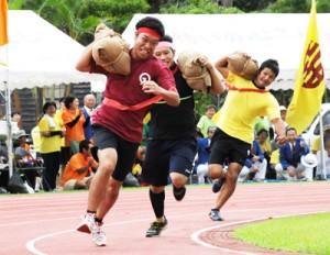 迫力のレースを繰り広げた「俵運搬」=9日、宇検村総合運動公園陸上競技場