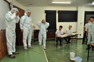 防護服の着用実演などを交え、防疫体制への手順を確認した研修会=5日、奄美市名瀬の県大島支庁