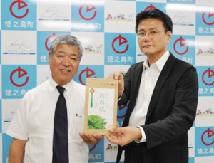 「向春草」を商品化した藤山社長(左)と臨床試験を行う大野准教授=24日、徳之島町