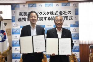 協定を結んだ朝山市長(右)と古俣社長=7日、奄美市役所