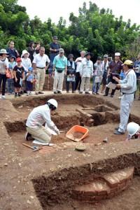 煙突と思われる遺構などが出土した久慈白糖工場跡(上)。工場跡から出土したアルファベッドの刻印のある英国製レンガ