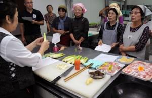 久留代表からマコモ料理を学ぶ参加者=29日、奄美市