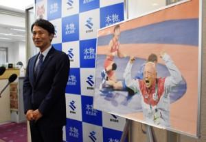 栄さんの写真を前に知事表彰の贈呈を発表する三反園知事=14日、鹿児島市の県庁