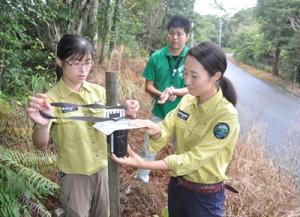 自動撮影装置を設置する岩本自然保護官(右)ら=22日、奄美市名瀬