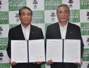 災害対策で協定を結んだ朝山市長(右)と高田理事長=8日、奄美市役所