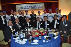 テーブルを回り参加者と記念撮影に応じるラミレス監督と選手ら=3日、奄美市名瀬の集宴会施設