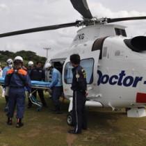 奄美ドクターヘリへの患者搬入を体験する訓練参加者ら=28日、和泊町