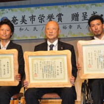 奄美市栄誉賞を受賞した(左から)里氏、栄氏、永田氏=21日、奄美市名瀬