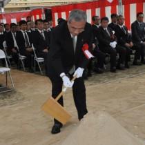 安全祈願祭でくわ入れの儀を行う朝山市長=28日、奄美市名瀬の建設現場