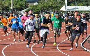 小学生から60代までが力走した男子年齢別800㍍リレー=13日、名瀬運動公園陸上競技場