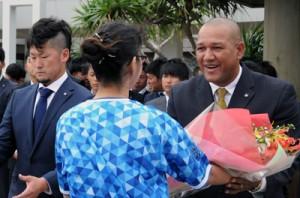 花束贈呈を受け取り、笑顔を見せるラミレス監督(右)と戸柱選手=1日、奄美空港