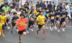 一斉にスタートする2㌔の出場者たち=27日、名瀬運動公園クロスカントリーコース