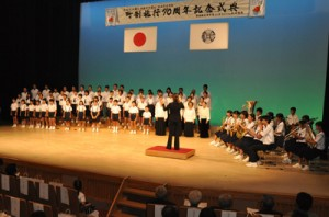 知名中学校吹奏楽部の演奏で、知名町町歌を斉唱する計70人のフローラル合唱団=6日、知名町おきえらぶ文化ホールあしびの郷・ちな