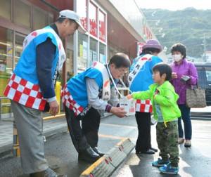 赤い羽根共同募金の街頭活動を行うボランティアら=3日、奄美市名瀬