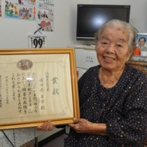 「母から子への手紙」コンテストで15周年記念賞を受賞した佐々木キヨさん。後ろに見えるのが貞進さんの写真=22日、和泊町
