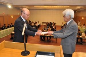舞台上で町広域協定認定手続きを行う運営委員会の奥山会長(左)と平安町長=1日、知名町