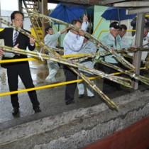 工場の圧搾機へと向かうコンベアーにサトウキビを投入する糖業関係者=1日、沖永良部島の南栄糖業