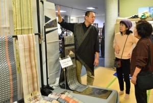 大島紬と博多織のコラボ作品などが並んだ合同展示会=23日、龍郷町