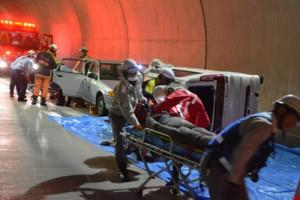 訓練で横転車両からけが人に見立てた人形を運び出す救急隊員ら=14日、網野子トンネル内