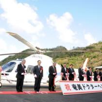 奄美ドクターヘリの前でテープカットをし、運航開始を祝う出席者=26日、奄美市名瀬