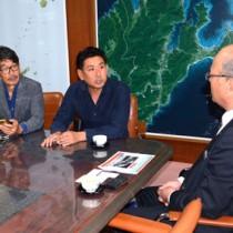 徳田町長に映画の概要を紹介する(左から)石川さん、後藤さん=19日、龍郷町長室