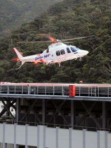 出動待機のため、県立大島病院救命救急センター屋上ヘリポートに着陸する奄美ドクターヘリ=27日午前8時すぎ、奄美市名瀬