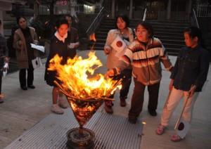 かがり火を囲み、復帰運動にまい進した先人のエネルギーに思いをはせる参加者=25日、奄美市