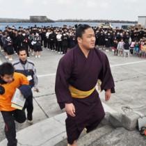 子どもたちに拍手で見送られ、船へと戻る石浦関=16日、和泊町手々知名の和泊港