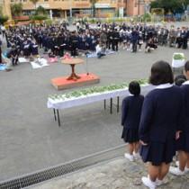石段(手前)に並んだ名瀬小児童の詩朗読に耳を傾ける出席者=25日、奄美市